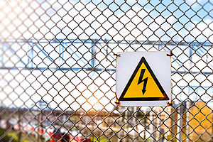 A high voltage warning sign is hanging on a chain-link fence