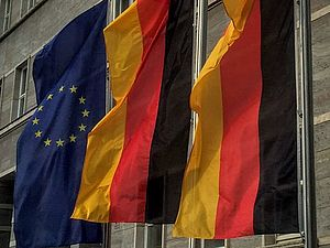 Two German flags and one European flag are waving on flagpoles