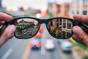 Two hands hold a pair of glasses in front of a blurry background. Through the glasses, the scenery of a city street is visible.